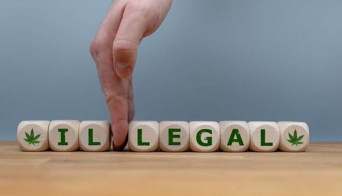 """A hand separates the prefix """"il"""" from the word """"illegal"""" spelled out in dice next to marijuana leaf symbols."""