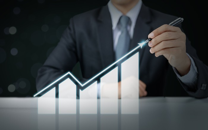 A person is pointing to a bar chart topped by an arrow that rises, then falls, then rises again.
