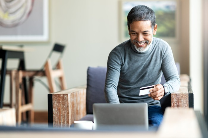 Man smiling while using his laptop and holding a credit card in his left hand.