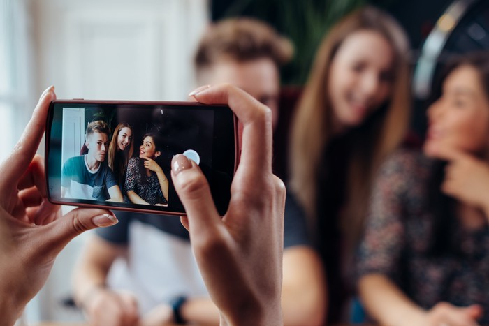 Person recording a video of a group of teens