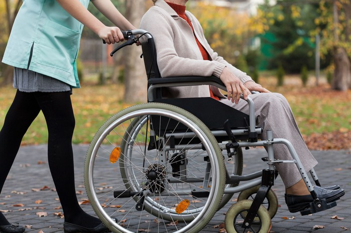 Older woman being pushed in a wheelchair by a caregiver.