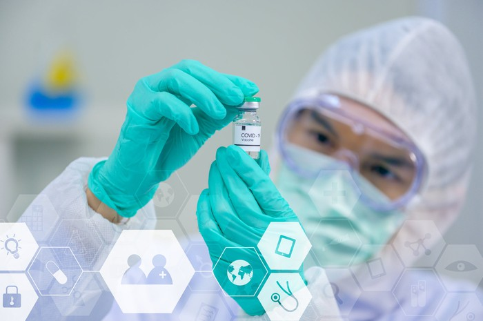 Scientist in protective gear holding a vial labeled COVID-19 Vaccine