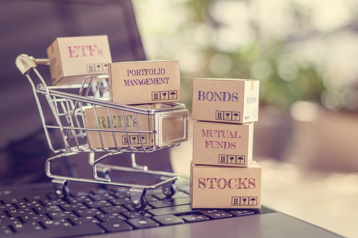 A mini shopping cart sits atop a laptop computer with boxes labeled ETFs, Portfolio Management, REITS and next to the cart a stack of boxes labeled Bonds, Mutual Funds, and Stocks.