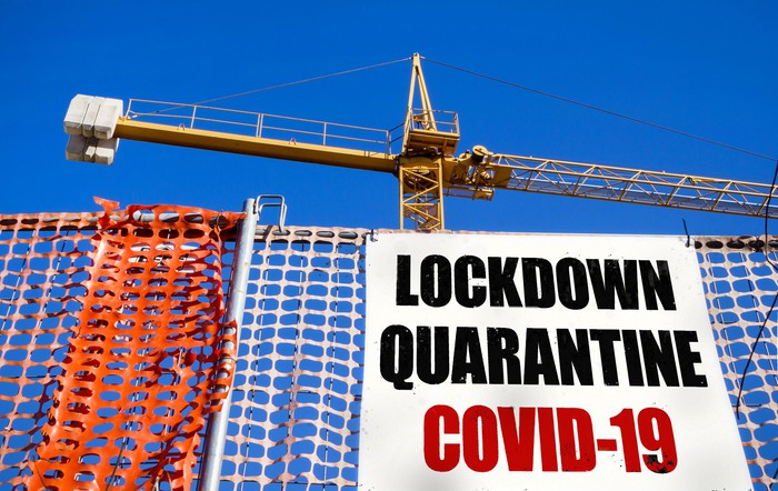A construction site with a billboard saying COVID-19 lockdown quarantine.