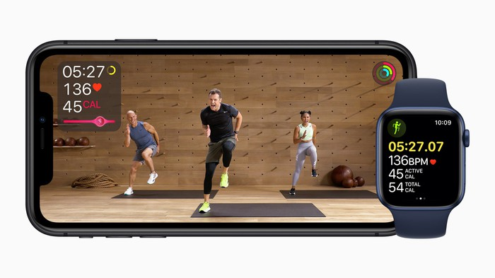 An iPhone plays a workout video while an Apple watch shows personal fitness data