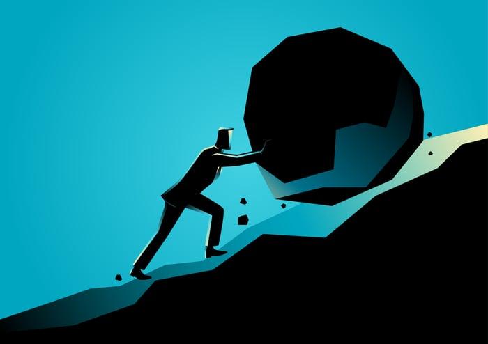 Businessman pushing a rock uphill