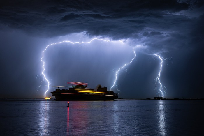 A large modern ship during a storm, with three strokes of lightning in the background.