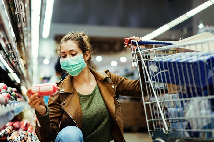 A shopper in a mask inspects a product in a grocery store.
