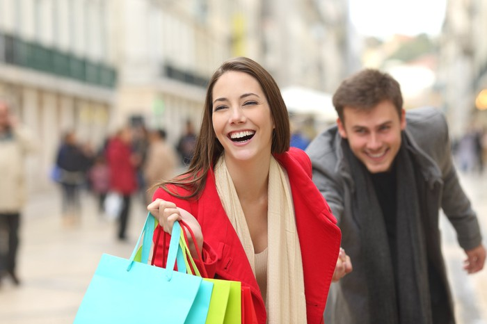 A young couple rushes through busy streets, smiling and carrying several shopping bags.