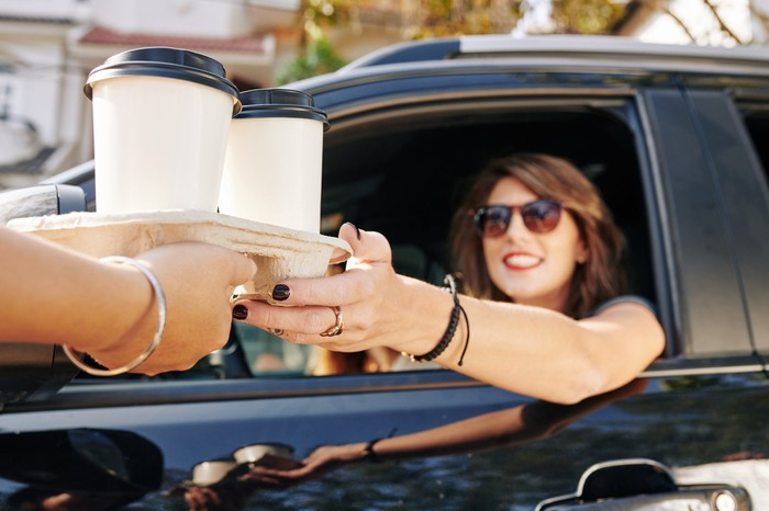 A smiling woman in a black sedan picking up coffee at a drive-through.