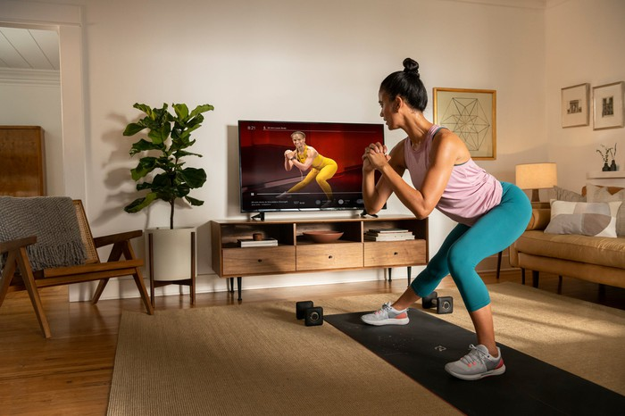 Woman on exercise mat in a living room following a Peloton workout on a TV