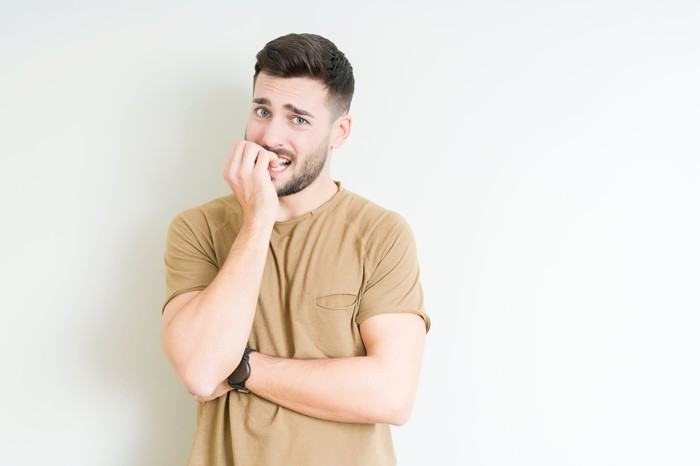 Man with nervous expression biting nails