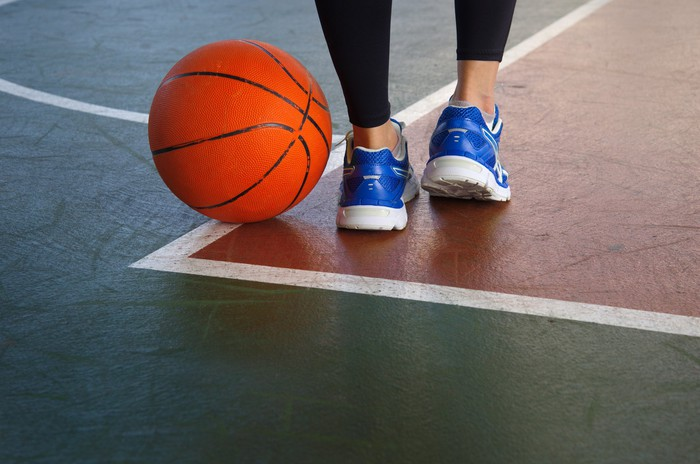 A woman in blue sports shoes standing next to a basketball on the court.