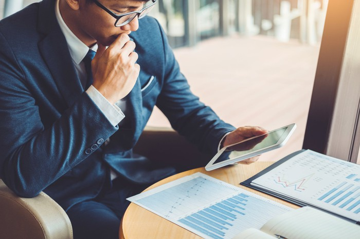 Businessman studying business graphs on his tablet
