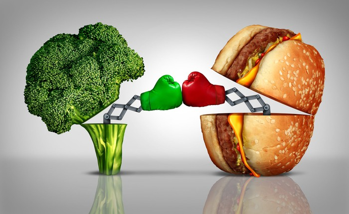A cheeseburger and a broccoli sparring with mechanical boxing gloves on.