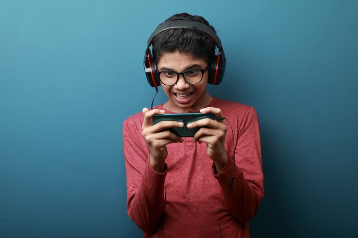 A boy plays a smartphone game.