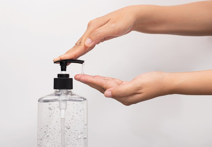 Woman dispenses hand sanitizer from a bottle