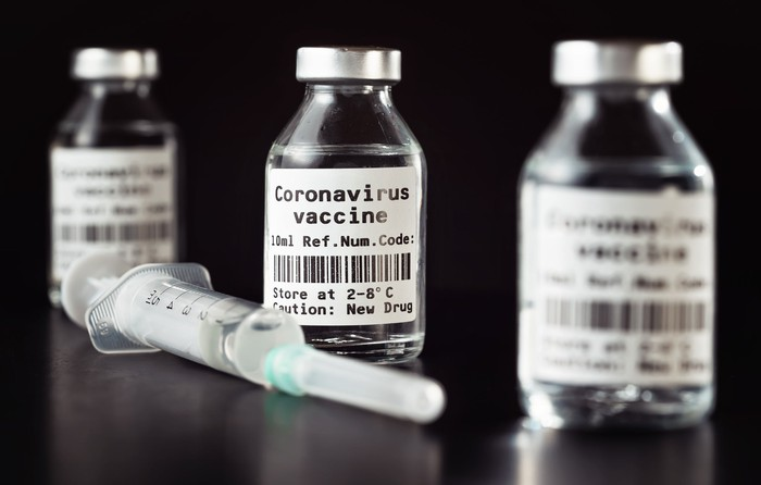 Three vaccine bottles that say Coronavirus vaccine next to a syringe.
