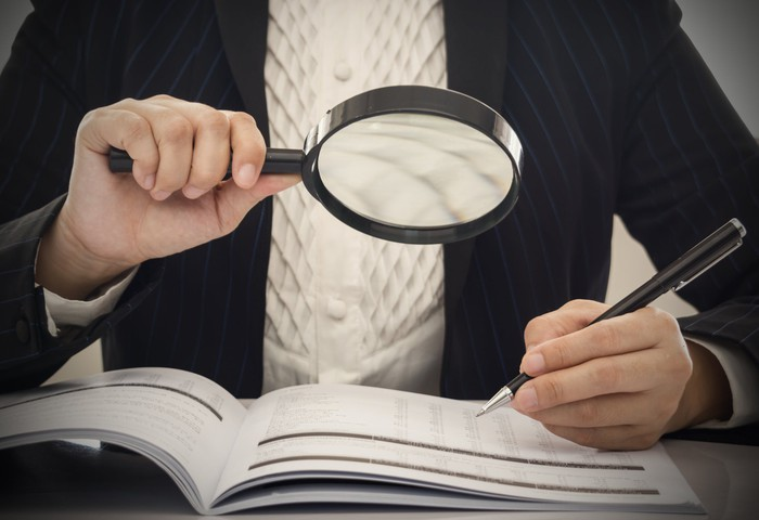 Auditor in business suit examines financial records with a pen and a magnifying glass