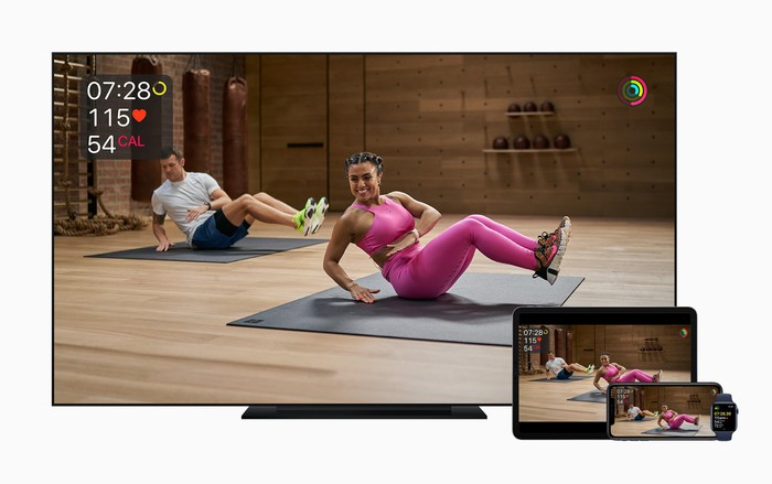 A TV, iPad, iPhone, and Apple Watch displaying a woman and man working out.