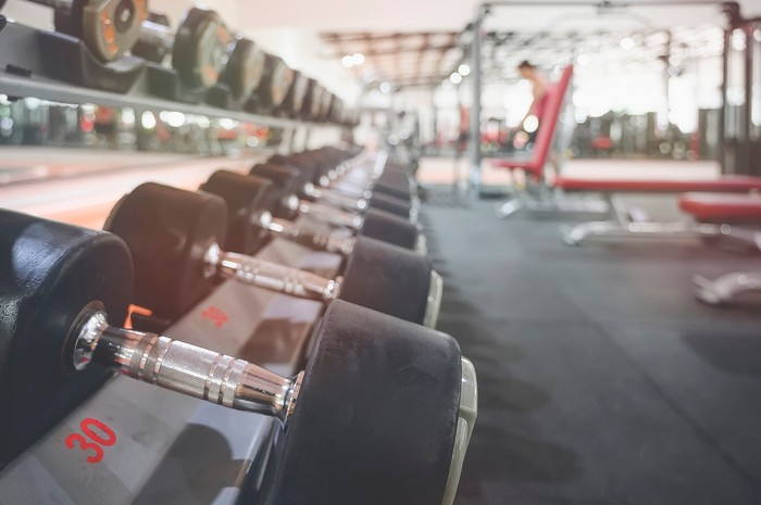 A mostly empty gym scene features a rack of free weights in the foreground.
