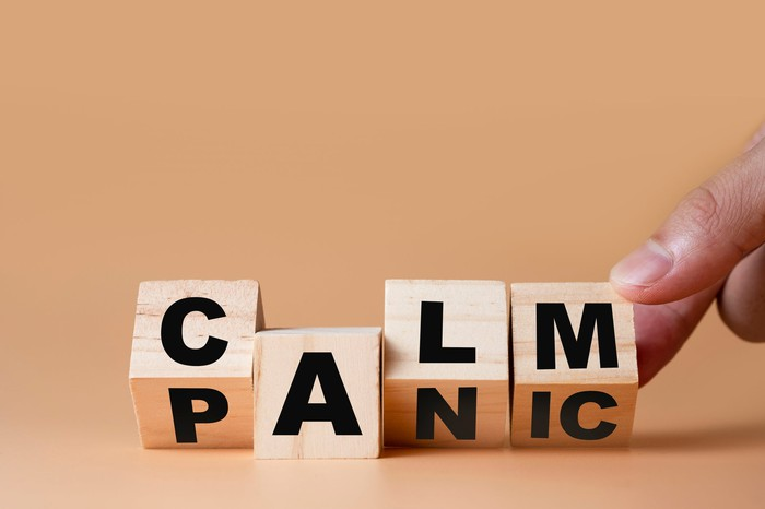 Wooden blocks with letters changing the word from panic to calm.