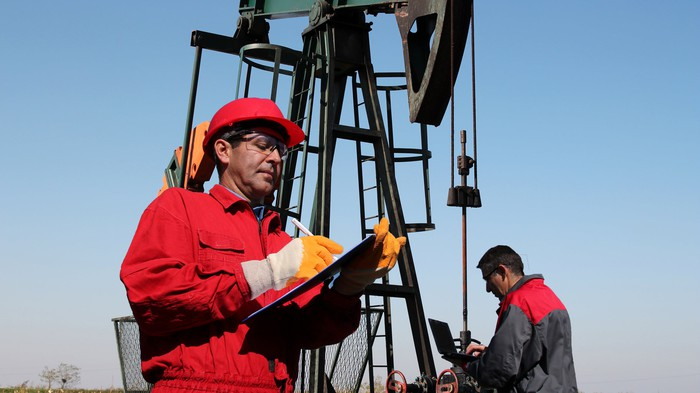 An oil well and two workers, one worker in the foreground writing in a notebook and the other in the background writing on a laptop.