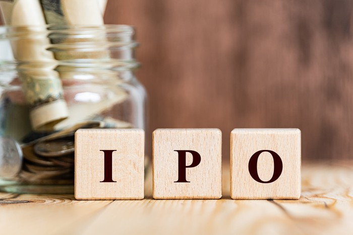 Wooden blocks spelling IPO with a jar of coins and paper currency in the background