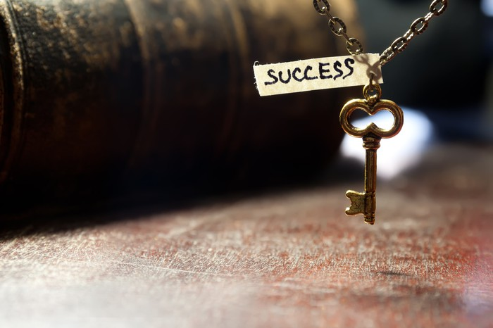 Old style skeleton key hanging from chain with the word success scrawled on a scrap of paper attached to the chain.