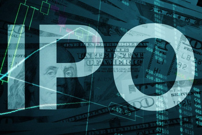 The letters IPO standing out over a dim background of hundred-dollar bills.