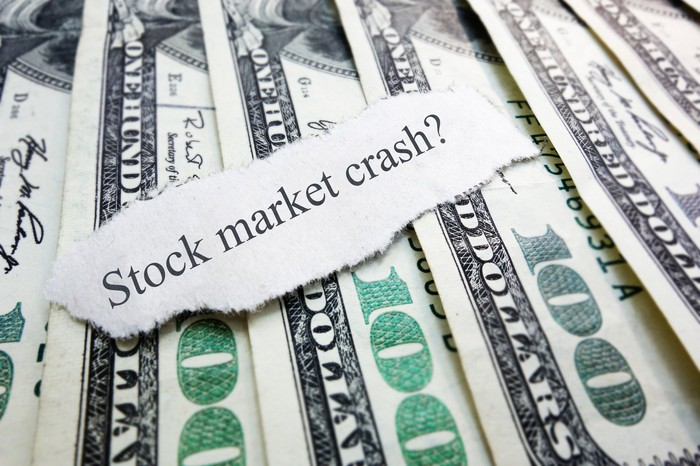 A fanned pile of one hundred dollar bills, with a sliver of paper laid atop that reads, Stock market crash?