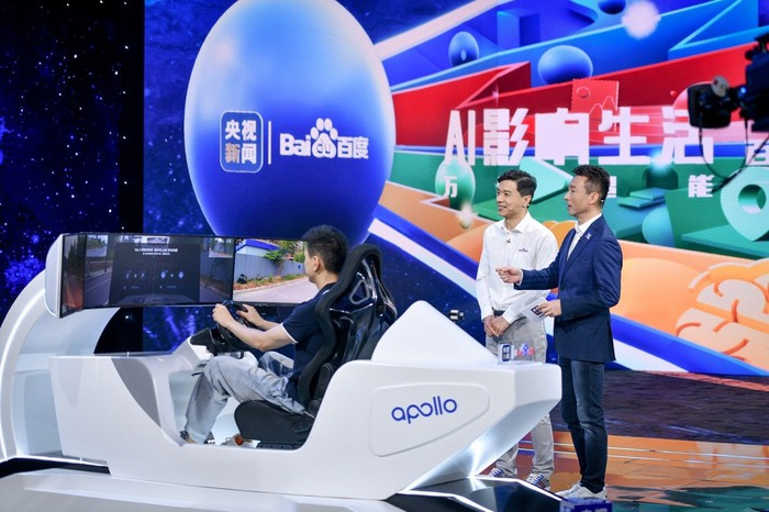 """Baidu CEO Robin Li watches a demonstration of Apollo's new """"remote driving"""" feature."""