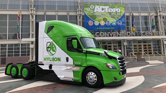 A green and white Freightliner semi truck with Hyliion's hybrid system installed.