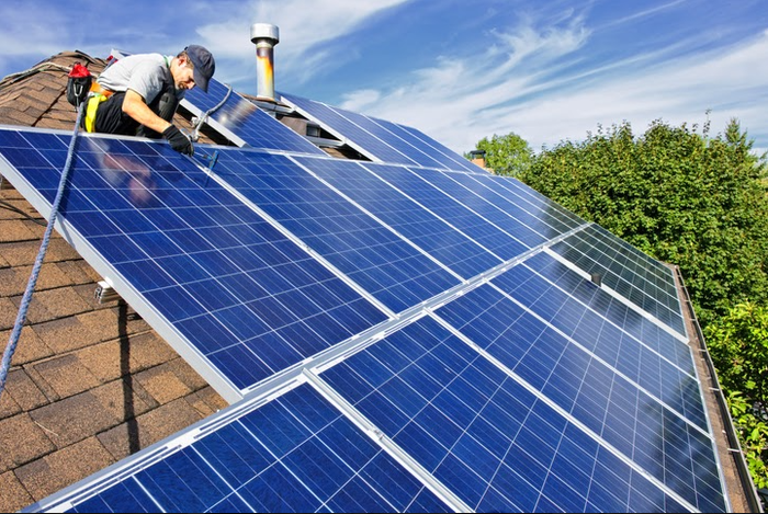 A worker installs solar panels on a residential roof.