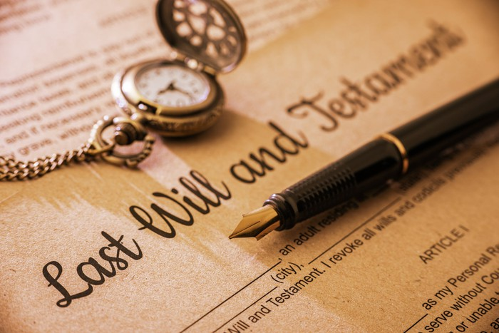 last will and testament with pen and watch.