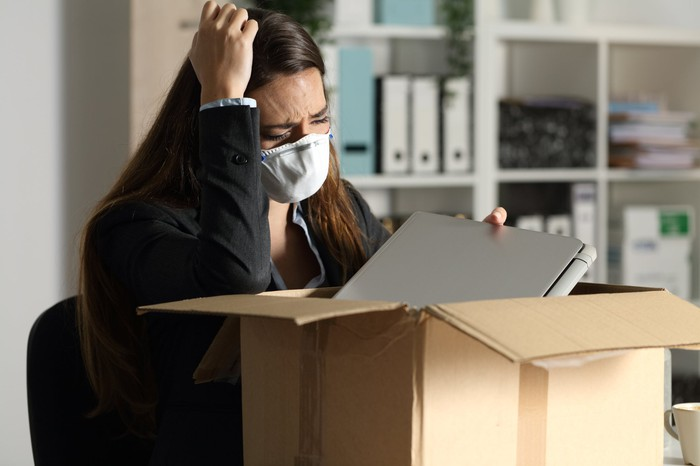 A woman wearing a mask and an anguished look on her face is packing a box.