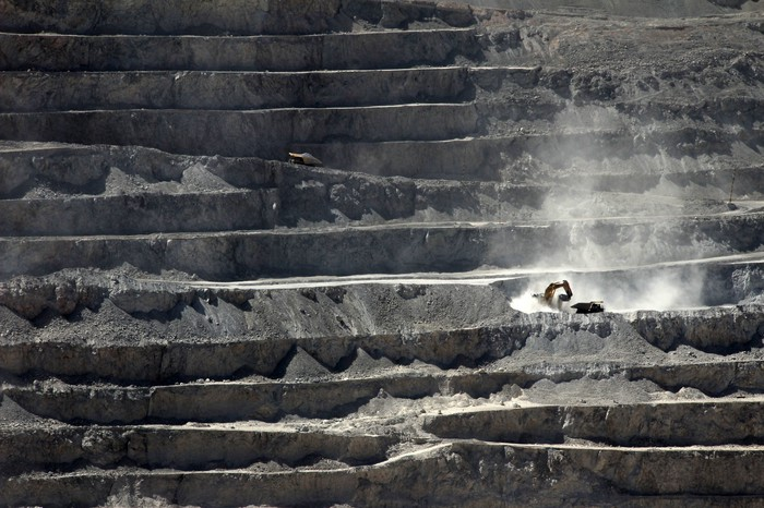heavy equipment digging at an open pit mine