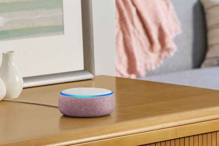 An Amazon Echo Dot on a side table.