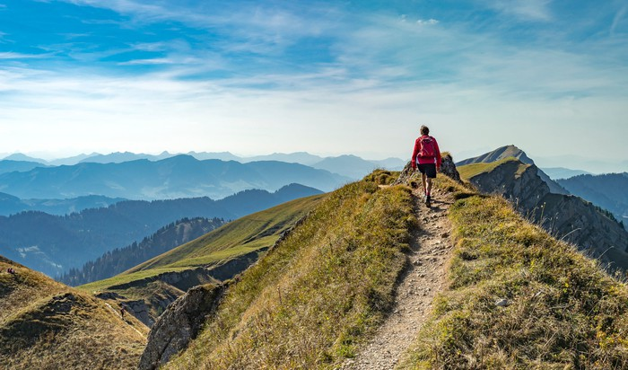 A person hiking on a path leading up to a hilltop with mountains in the background.