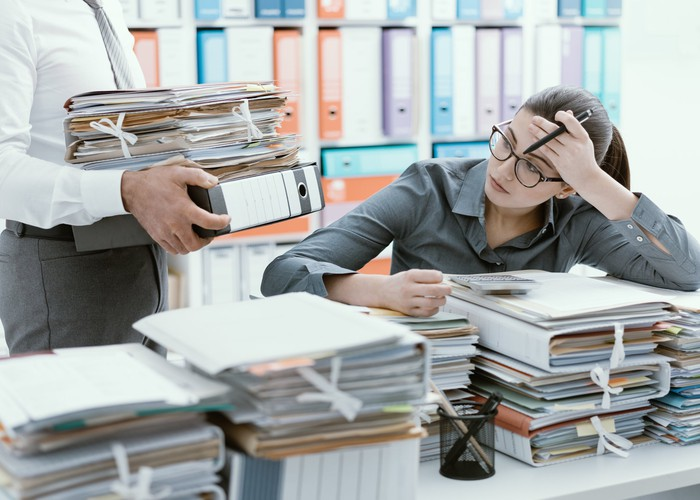 A frustrated woman with a desk full of paperwork and a coworker bringing more