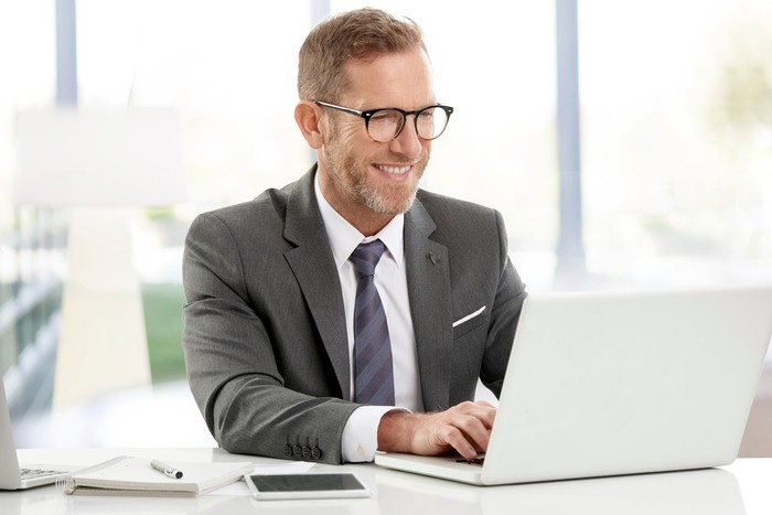 Smiling man in business suit typing on laptop