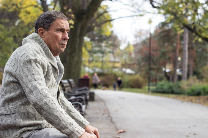 Older man in sweater with serious expression, sitting on park bench.