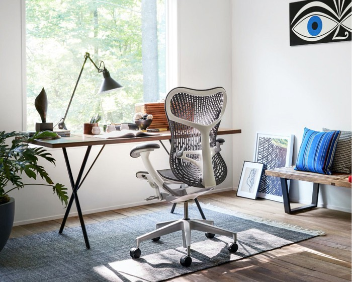 "A Herman Miller ""Mirra 2"" chair faces a contemporary desk and window in a home office."