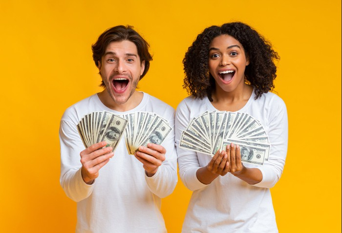 A young man and woman hold handfuls of $100 bills.