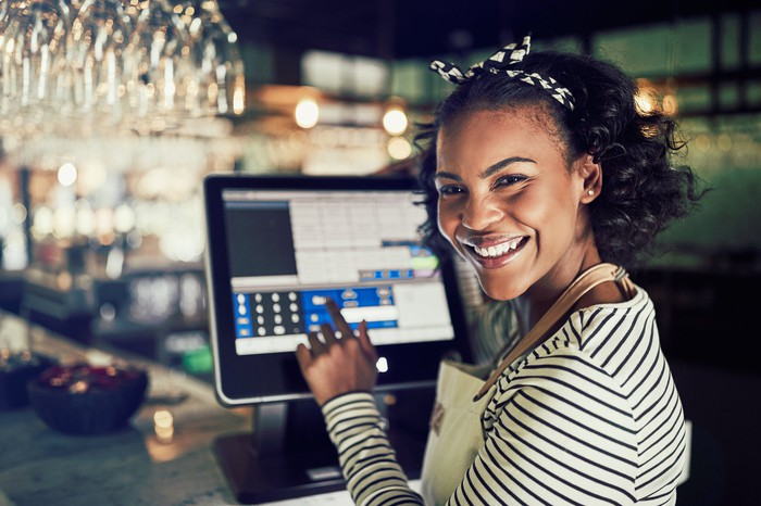 A smiling cashier using a touchscreen point-of-sale device in a retail store.