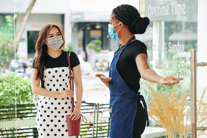 A cafe owner welcomes a customer during COVID-19; both are wearing masks.