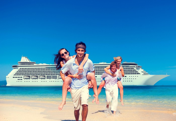 Two couples frolicking on the shoreline of a beach with a cruise ship behind them.