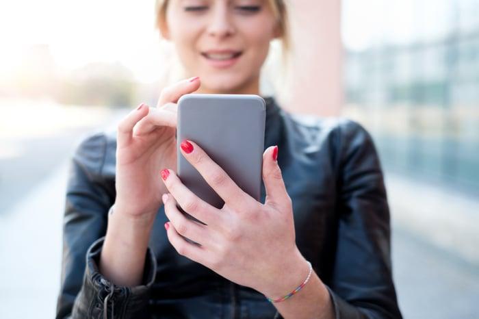 A woman uses a smartphone.
