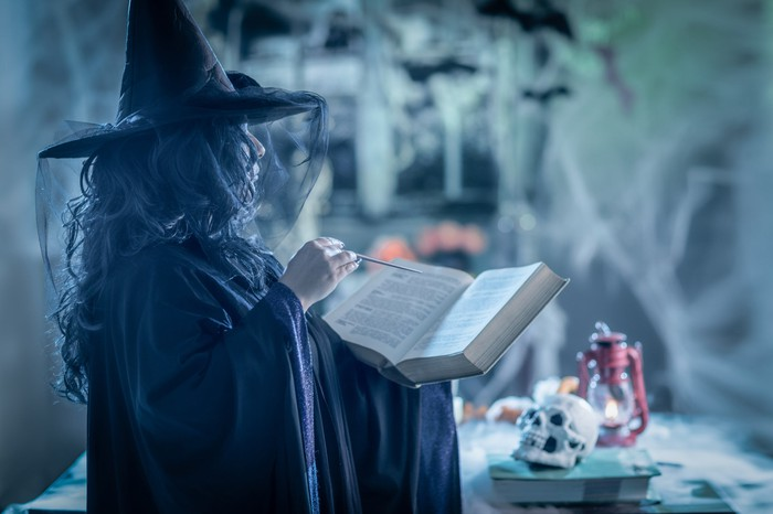 Person wearing pointed witch's hat holding book, with skull and other creepy things nearby.