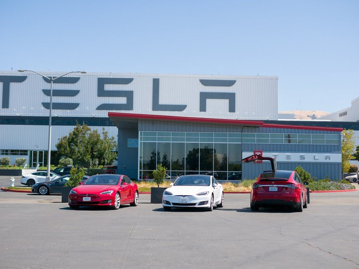 Three Tesla cars in parking lot in front of Tesla factory.